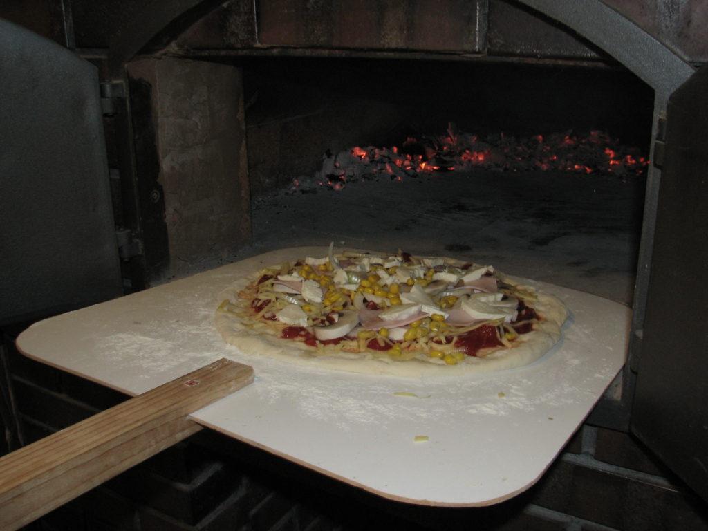 Pizza na łopacie przed włożeniem dopieca chlebowego.